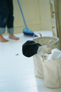 ランドリーバスケットと床を掃く人の写真素材 [FYI03229141]