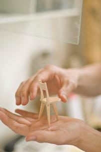 イスの模型を手の平に乗せる男性の手元の写真素材 [FYI03229500]
