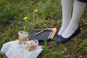 コーヒーとサンドイッチとノートと女性の足元の写真素材 [FYI03229603]
