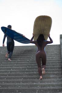 ウエットスーツを着てサーフボードを持つカップルの写真素材 [FYI03229643]