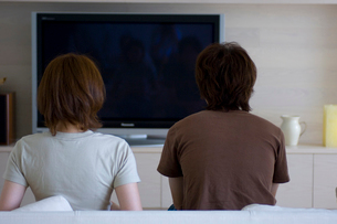 ソファーに座るカップルとテレビの写真素材 [FYI03229735]