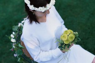 花輪を巻いて椅子に座った女性の写真素材 [FYI03229918]