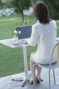 パソコンに向かう女性の後姿の写真素材 [FYI03230024]