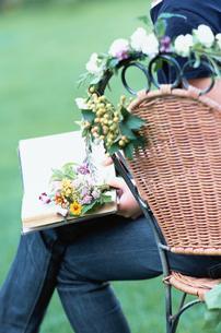 庭のイスの上で読書をする女性の写真素材 [FYI03230067]