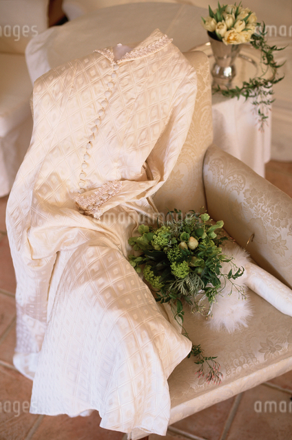 白いソファの上のドレスとフラワーアレンジメントの写真素材 [FYI03230100]