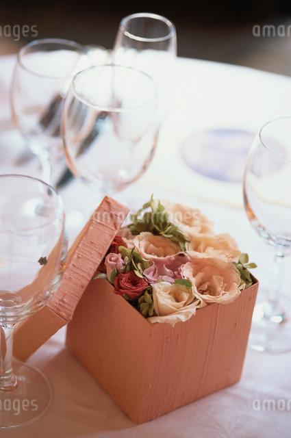 テーブルの上のグラスと箱に入った花の写真素材 [FYI03230120]
