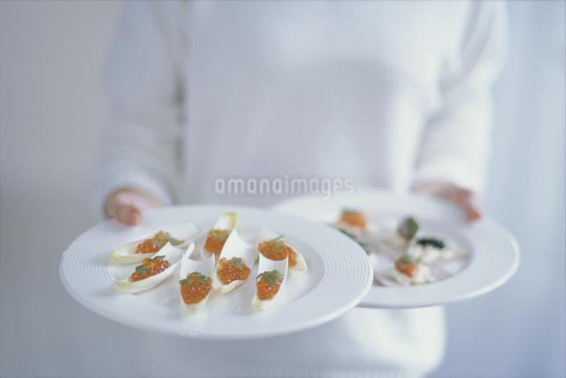 白い皿に盛った料理を差し出す手の写真素材 [FYI03230133]