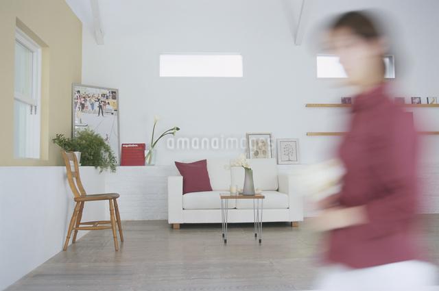 リビングを歩く女性の写真素材 [FYI03230223]