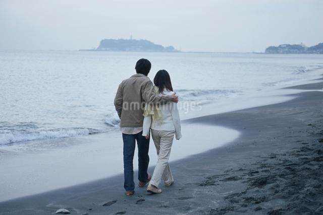 砂浜を歩く日本人カップルの後ろ姿の写真素材 [FYI03230343]