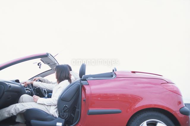 赤い自動車に乗る日本人カップルの写真素材 [FYI03230374]