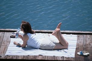 敷物の上に寝転ぶ日本人女性の写真素材 [FYI03230395]