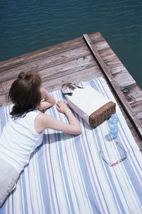 敷物の上に寝転ぶ日本人女性の写真素材 [FYI03230398]