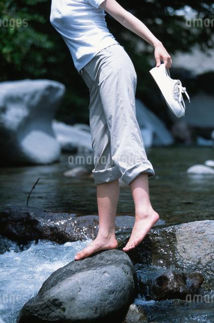 水辺の岩に立つ日本人女性の写真素材 [FYI03230413]