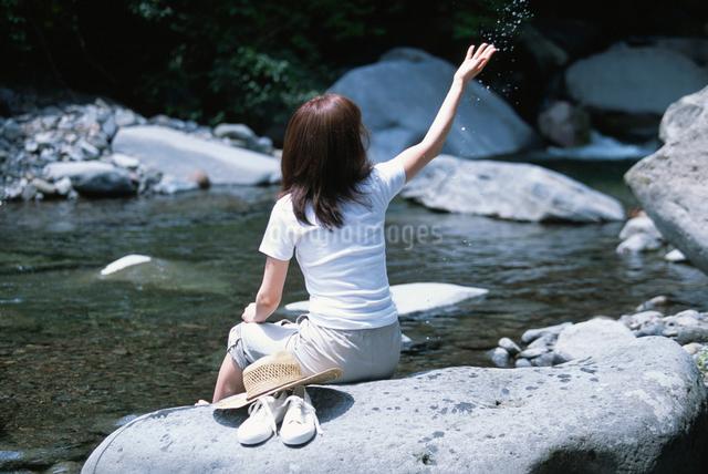 水辺の岩に座る日本人女性の写真素材 [FYI03230415]