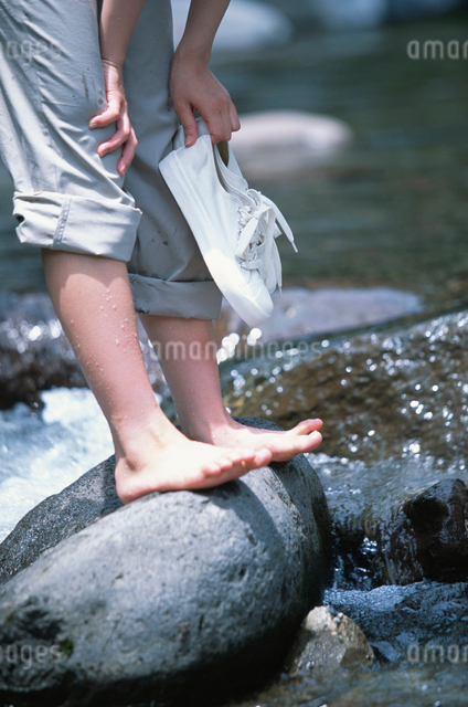 水辺の岩に立つ日本人女性の写真素材 [FYI03230418]