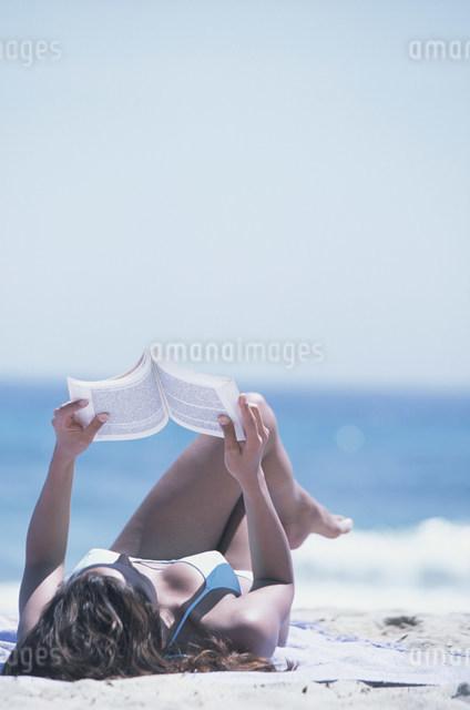 砂浜で本を読む外国人女性の写真素材 [FYI03230440]