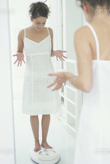 体重計に乗り驚く女性の写真素材 [FYI03230446]