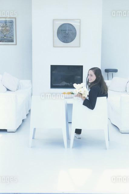 カラーを持ち白いイスに座る外国人女性の写真素材 [FYI03230492]