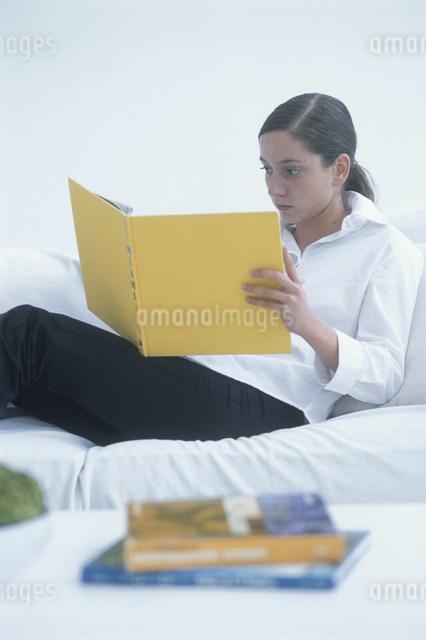 ソファに座り黄色い表紙の本を読む外国人女性の写真素材 [FYI03230495]