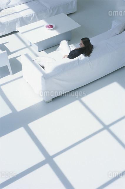 白いソファに座る外国人女性の後姿の写真素材 [FYI03230496]