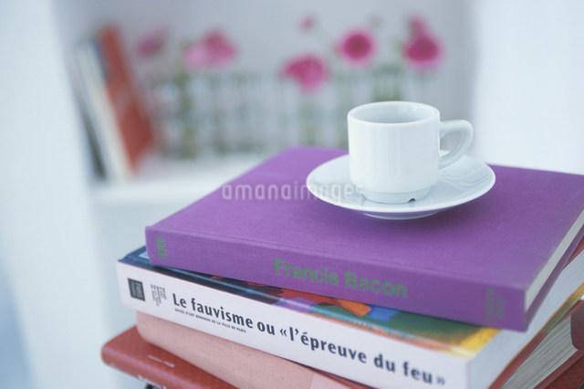 重ねた本の上の白いカップとソーサーの写真素材 [FYI03230497]