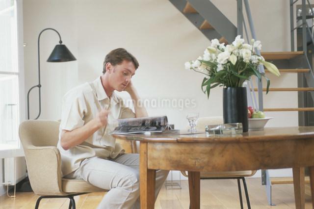 椅子に座り本を読む外国人男性の写真素材 [FYI03230503]