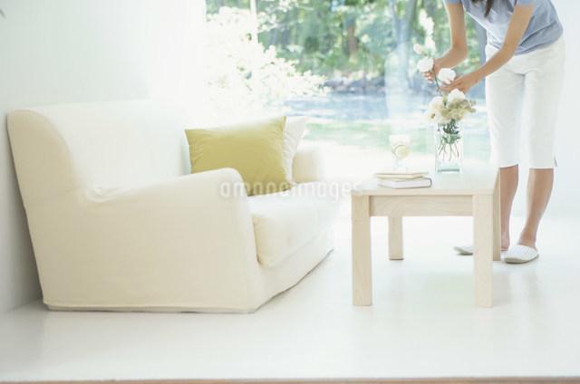 白いソファとテーブルに花を飾る女性の写真素材 [FYI03230508]