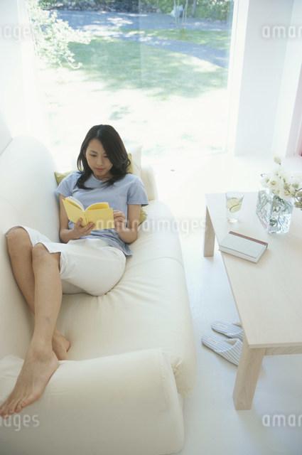 白いソファに横になり本を読む日本人女性の写真素材 [FYI03230509]