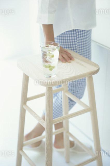 グラスの載った椅子の脇を歩く女性の写真素材 [FYI03230510]