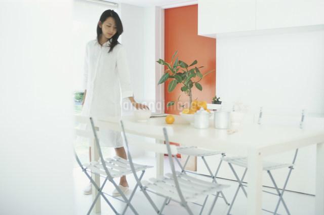 ダイニングテーブルの新聞を取る日本人女性の写真素材 [FYI03230511]