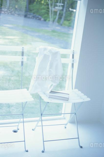 窓辺にあるシャツと本を置いた椅子の写真素材 [FYI03230513]