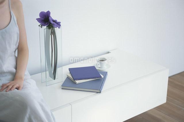 棚に座る女性と横に置いた紫の花と本の写真素材 [FYI03230515]