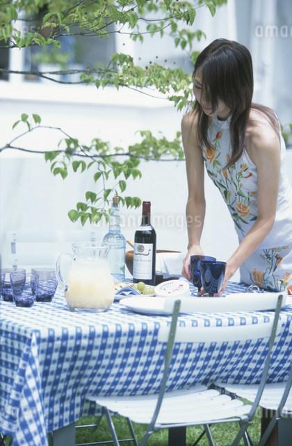 庭でテーブルセッティングする日本人女性の写真素材 [FYI03230525]