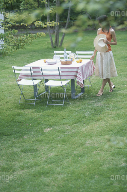 庭でテーブルセッティングする日本人女性の写真素材 [FYI03230526]