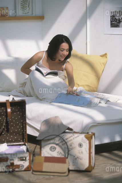 ベッドの上で地図を見る日本人女性の写真素材 [FYI03230527]