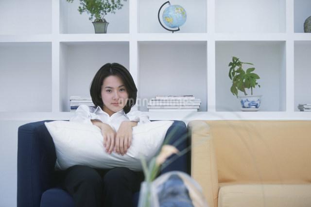クッションを抱えてソファに座る日本人女性の写真素材 [FYI03230528]