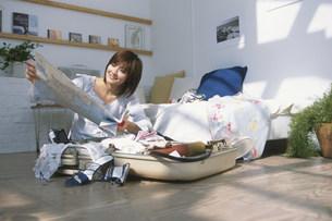 旅支度をして地図を見る日本人女性の写真素材 [FYI03230534]