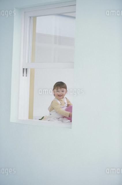窓越しに見える部屋で遊ぶ幼児の写真素材 [FYI03230536]