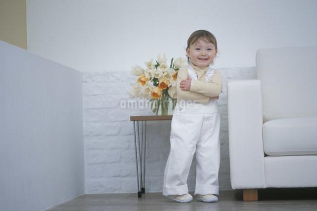 白いソファのそばで笑顔の幼児の写真素材 [FYI03230539]