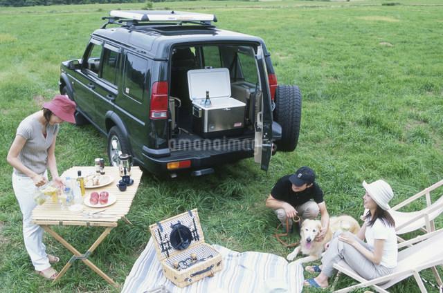 ピクニックをする日本人男女3人グループと犬の写真素材 [FYI03230545]
