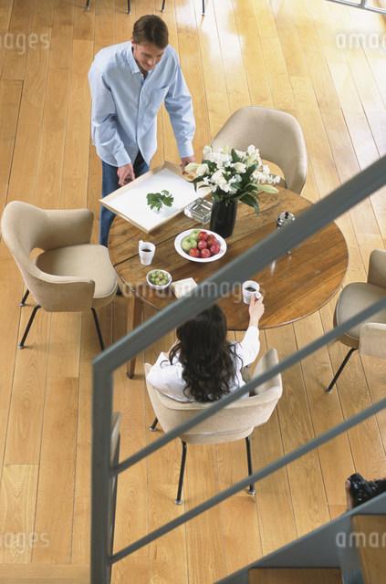 テーブルで寛ぐ男女の写真素材 [FYI03230553]