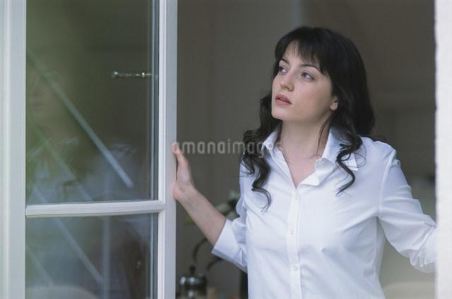 窓から外を眺める女性の写真素材 [FYI03230557]