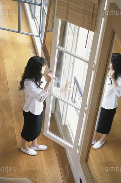 窓を開けて外を見る女性の写真素材 [FYI03230559]