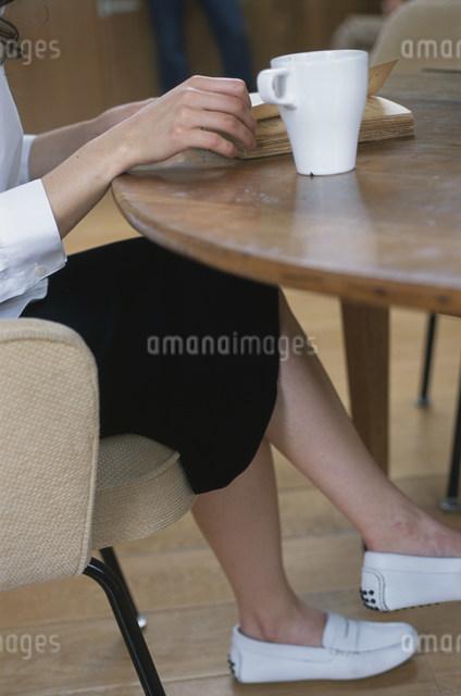 イスに座って本を読む女性の写真素材 [FYI03230560]