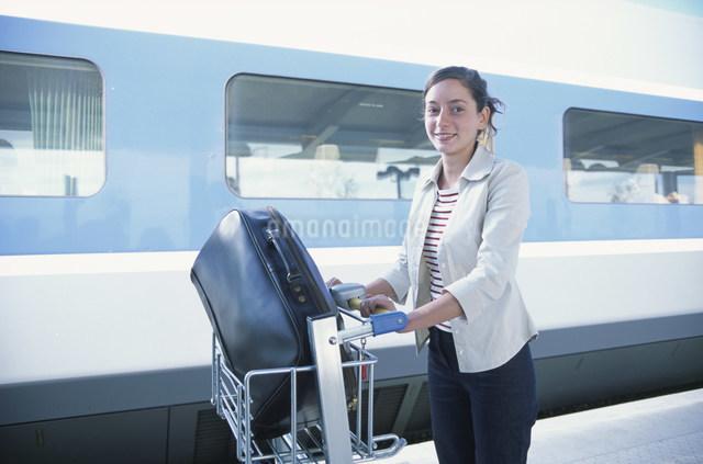 バッグを乗せたカートを運ぶ女性の写真素材 [FYI03230572]