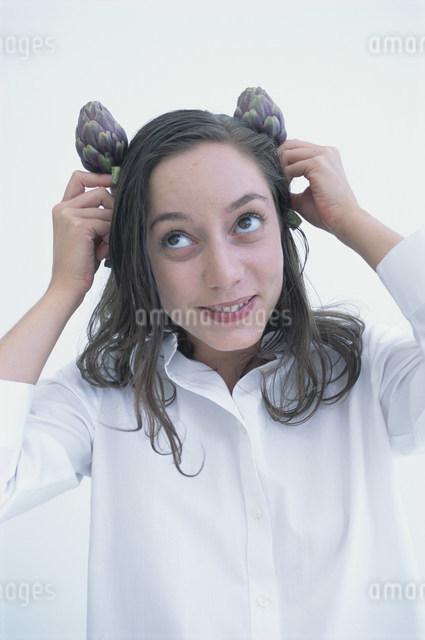 頭の両サイドでアーティチョークを持つ女性の写真素材 [FYI03230581]