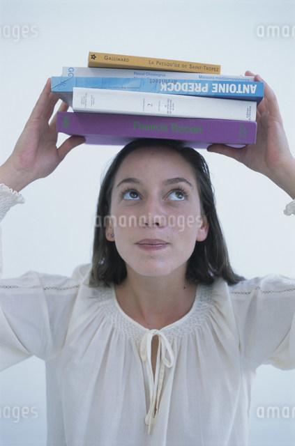 本の束を頭の上に乗せた女性の写真素材 [FYI03230584]