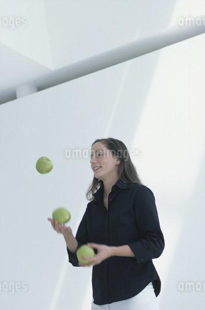 青リンゴを投げて遊ぶ女性の写真素材 [FYI03230588]