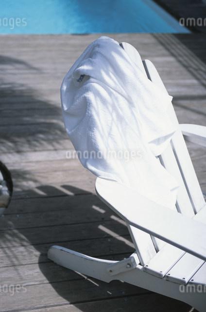 プールサイドのチェアに掛けられたバスローブの写真素材 [FYI03230598]