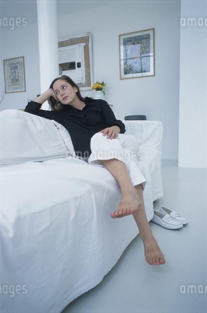 リビングルームの白いソファで寛ぐ女性の写真素材 [FYI03230604]